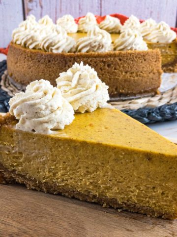 Perfect slice of pumpkin cheesecake on wooden platter
