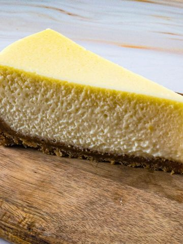 Slice of the Ultimate Original Cheesecake on a wooden plate